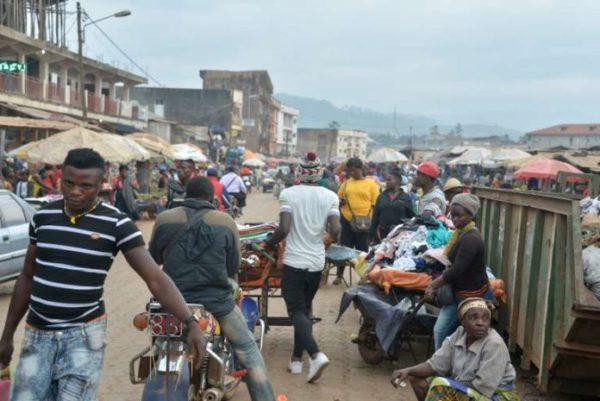 """La gente camina por el mercado de Bamenda el 15 de noviembre de 2017, después de que una bomba casera explotase en la noche del 12 de noviembre. Las autoridades camerunesas impusieron un toque de queda el 8 de noviembre de 2017 y ordenaron el cierre de establecimientos y espacios públicos en la ciudad principal de una región agitada por las tensiones entre la minoría anglófona del país. Cuatro bombas improvisadas explotaron durante la noche del 12 de noviembre, una semana después de que cuatro soldados fuesen asesinados en las dos regiones en las que reside la mayor parte de la minoría anglófona de Camerún. Las autoridades culparon de sus muertes a los """"terroristas"""". Los anglófonos defienden la secesión de las dos regiones anglófonas, la del Noroeste y la del Sudoeste, de Camerún. Fuente: AFP"""